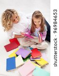 Selecting a story to read - woman and little girl with lots of books - stock photo
