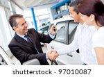 Couple buying a car and salesman handling keys - stock photo