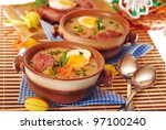 white borscht with egg and grilled sausage in stoneware bowls for easter dinner - stock photo