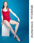 Ballerina Posing in Red Leotard and Point Shoes Isolated Against a Blue Background - stock photo