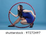 Beautiful woman in a sport wear. Dance hoop gym exercises blue background - stock photo