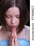 Thoughtful praying young girl - closeup portrait on dark background - stock photo