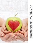 Healthy nutrition concept - hands holding apple with heart cutout - stock photo