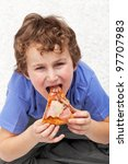 Hungry kid eating pizza sitting on the floor - stock photo