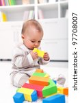 Baby girl playing with colorful blocks - stock photo