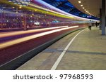 night photo of a departing train at the train station with motion blur - stock photo