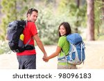 Hikers. Hiking young couple walking in forest during camping travel hike. Healthy lifestyle photo of Asian woman and Caucasian man holding hands. - stock photo