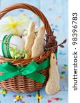 Easter bunny cookies, eggs with ribbon in a basket on an blue  wooden board. - stock photo