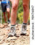 Hiker. Hiking shoes close up outdoors during hike - female shoes. Hikers in the background - stock photo