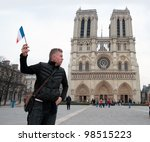 man with french flag in front of Notre Dame - stock photo