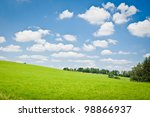 green farm land with a blue sky - stock photo