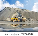 Excavator and truck in mine. - stock photo