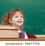 Cheerful smiling child with a book and apples against blackboard  in a class . Looking at camera. School concept - stock photo