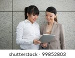 Two Asian women using a digital tablet PC. - stock photo