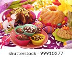 assortment of easter confectionery ( ring cakes,muffins ) on colorful festive table - stock photo
