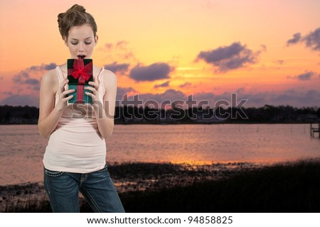 A beautiful teenage woman opening a Christmas, birthday or Valentines day present - stock photo