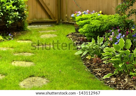 A beautifully landscaped back yard with stepping stones. - stock photo