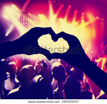 a crowd of people at a concert with heart shaped hands over the stage toned with a retro vintage instagram filter  - stock photo