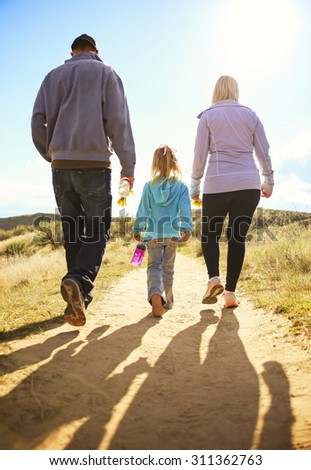 a cute family walking into the sunset on a nature hike along a dirt trail toned with a retro vintage instagram filter app or action  - stock photo
