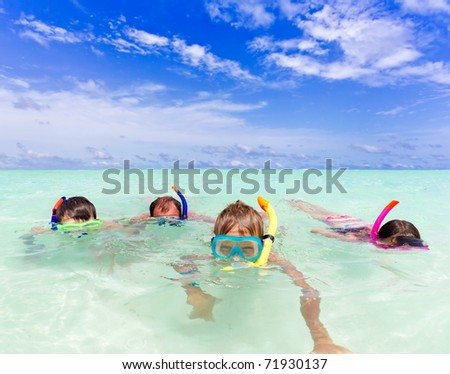 A family snorkeling in the ocean. - stock photo