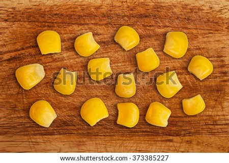 A few grains of canned corn on a wooden table. Sweet whole kernel corn - stock photo