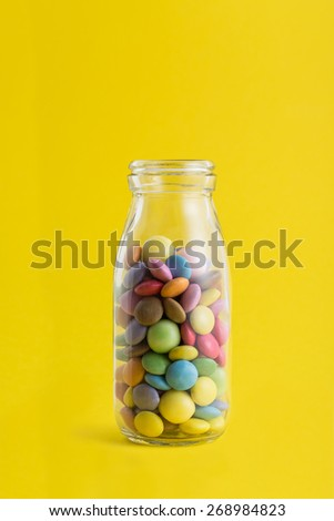 A Glass Bottle Full of Colorful Chocolate Coated Candies on a Yellow Background.  - stock photo