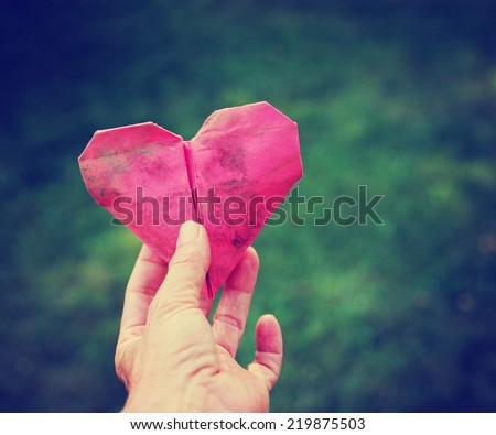 a hand holding an origami heart over green grass toned with a retro vintage instagram filter (shallow depth of field) - stock photo
