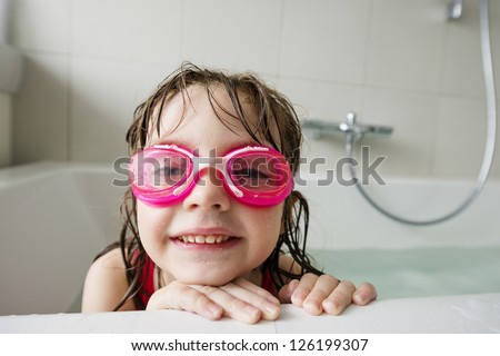 a happy  little girl with swim glasses bathing - stock photo