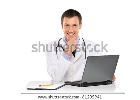 A happy young doctor working on a laptop against white background - stock photo