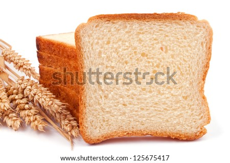 A heap of bread slices and one slice like a copy space, leaning on the heap and wheat ears - isolated on white - stock photo