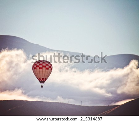 a hot air balloon in the sky in front of clouds  - stock photo