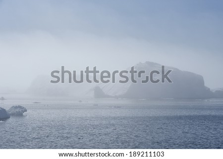 A huge iceberg looms out of the fog in Disko bay. These icebergs are calved by the Jakobshavn glacier, and usually float North with the currents, eventually turning south and down into the Atlantic.  - stock photo