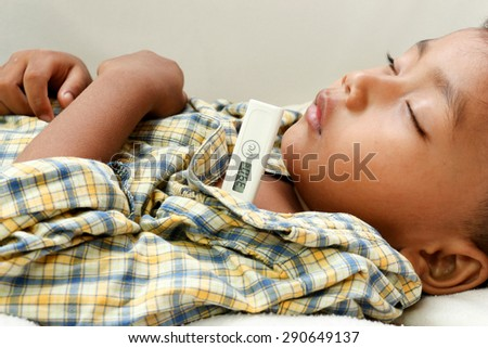 a little boy who has fever.focus at a temperature. - stock photo