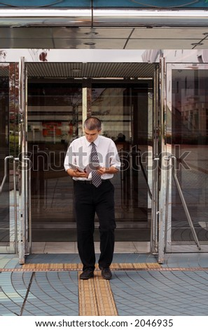 A man (businessman or student....) reading with attention a notebook while is walking out from a modern building(corporate or library..... ) - stock photo