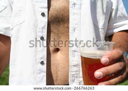 a man holding a beer in a cup with a bare belly - stock photo