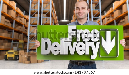 A man holding a Free delivery board in a distribution warehouse - stock photo