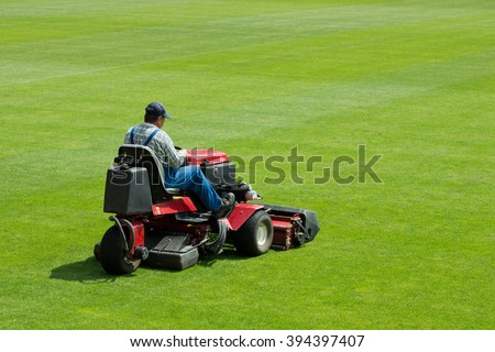 A man mowing the grass on a football stadium. - stock photo