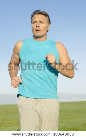 A mature forties man jogging in blue shirt - stock photo