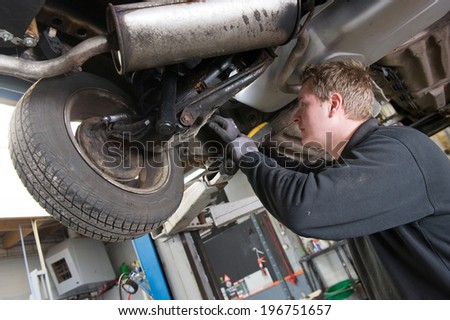 A mechanic is checking the technical state underneath a lifted car on a bridge in a garage. - stock photo
