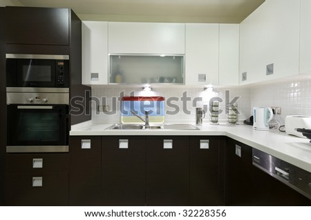 A modern kitchen with sleek brown cabinets and a beautiful white  complete with a stainless steel dishwasher, oven and microwave set. - stock photo
