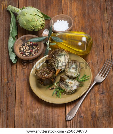 A plate with cooked artichokes decorated with fresh rosemary on wooden  - stock photo