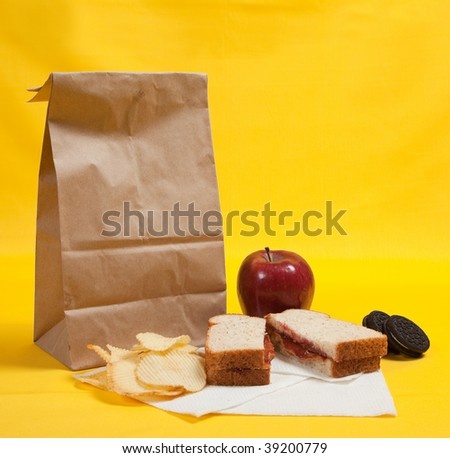 A sack lunch with peanut butter sandwich with apple, chips and cookies - stock photo