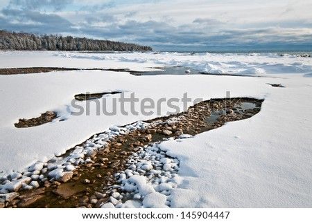 A spring flowing into Lake Michigan creates a small area of open water on the winter shoreline of Newport State Park in Door County, Wisconsin. - stock photo