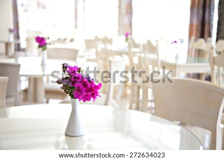 a table with beautiful flowers on a cafe - restaurant  on a hotel with blurry background - stock photo