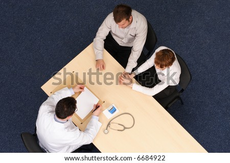 A top view of a couple sitting opposite a doctor at his table during a medical consultation. doctor talking about medical record - stock photo