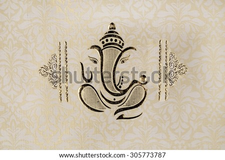 a traditional indian wedding invitation card - colorful, textured ,bold and beautiful well decorated embossed with lord ganesha and a sanskrit shloka - stock photo