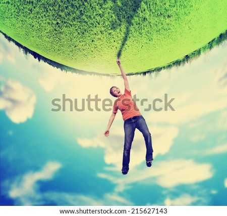 a woman doing a cartwheel on an upside down planet world of green grass toned with a vintage retro instagram like filter  - stock photo