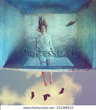 a woman in a dress made of book pages in a box under water with the sky beneath her  - stock photo