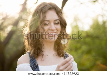 A woman looks at a dandelion, close-up portrait. The girl smiles. Sunset Park. - stock photo