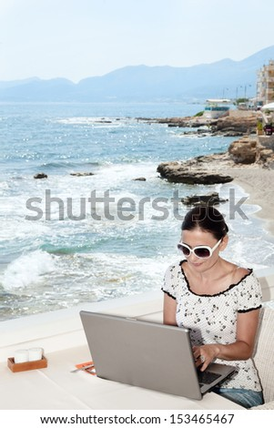 A woman sends a message on your laptop in a seaside cafe - stock photo
